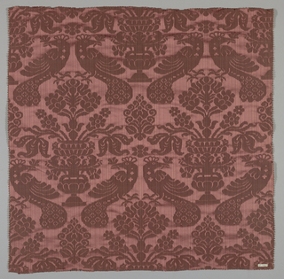 Reproduction fabric inspired by a sixteenth century design in the Cooper Union Museum collection. In dark purple with a pattern of flower-filled urns and pairs of peacocks.