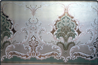 Large-scale medallions, on lattice-like base, alternating with much smaller medallions. Acanthus scrolls connect the elements. Printed in green, brown, pink and white on taupe ground.
