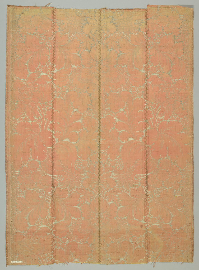 Large scale symmetrical design of fruit, flowers, leaves and arabesques in silver on various twill bindings.