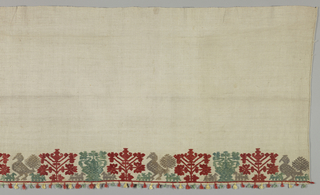 Bed curtain of hand-spun undyed linen, embroidered with a border of tree of life, peacock, and dog motifs in red, beige and green silks. With tassels.