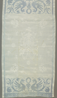 Rectangular white damask towel with figural cartouche in center surrounded by detached flowers and blue border with late 16th century style dragons facing an urn.