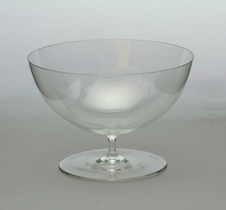 Thin-walled, clear glass; hemispherical bowl supported by thin stem on flat, circular foot.