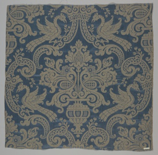 Dark blue and beige reproduction textile inspired by a sixteenth century example in the Cooper Union Museum collection. Design has a large-scale symmetrical design of a flower-filled urn surrounded by scrolling bands with perching peacocks. Warp threads vary slightly in tone to simulate the appearance of a historical textile.