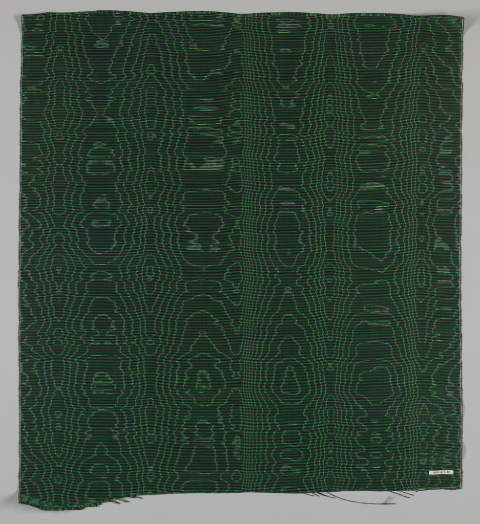 Fragment of Irish poplin. Narrow horizontal stripes of black and green. Watered.   The texture of this fabric is the result of a closely set fine silk warp and a thick stiff wool weft to produce ribs; the fine color bands by an alternation of green and purple warps; and the pattern (moire) by the effect of water as the fabric was roller under pressure between two rollers on rotating slightly more than the other.