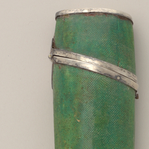 Case for three implements, oval in section. Green painted shark skin. Lid attached to body with hinge and lock. Silver mounts. Inside covered with red silk.