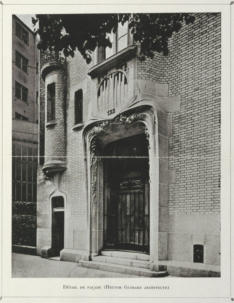 A photograph of the front entrance and facade of Hector Guimard's house. The glass doors are protected by decorative grillework. The protruding frame of stone has decorative designs carved in. The principal facade is composed of brick.