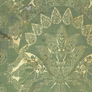 Length of woven silk in green and ivory with symmetrical pattern reversed along vertical axis. Design shows elaborate plant forms and pomegranate motifs crowned with foliate scrolls. Both selvages present.