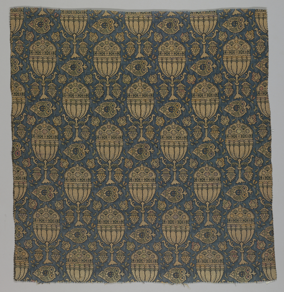 Reproduction textile with a design of a stiff conventionalized tree with leaves scattered over a dark ground. Adapted from from a medieval Italian textile in the Cooper Union Museum collection.