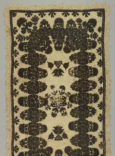 An oblong panel, probably an All Souls Day mat, of heavy cream colored hand-woven linen, embroidered in black wool. Edged with cream linen needle lace. Design is a star-shaped central motif encircled by stylized floral forms. Two detached motifs of lotus flowers rising from a triangular form. Wide border consists of detached highly stylized flower forms, carnation and lotus, bi-laterally symmetrical, ranged on either margin of a narrow band, of stylized curving vine design. Border is narrow band with detached stylized leaf forms.