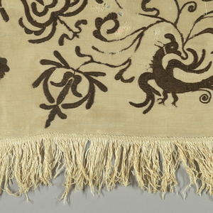 """Four natural linen rectangular fragments sewn together, each embroidered in brown wool showing a bird in a scrolling branch with exotic blossoms. Two panels the mirror image of the other. Length of weft-loop fringe of about 3"""" sewn to three sides."""