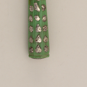 Four curved tines, curved shoulders and long baluster neck, Plain oval ferrule. Flaring ivory handle, painted green, octagonal in section, carved with vertical lines. Small silver appliques, floral and leaf-shaped, on front and back. Silver mount on top of handle showing a lion.
