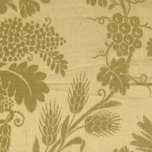Fragment of a large scale symmetrical pattern reversed on the center line of the textile. An urn with flowers placed in offset rows connected by a curving vine (almost an ogee framework) having grape vines and heads of wheat. Background is a dull salmon and the pattern is yellow twill. Intact selvage on right side.