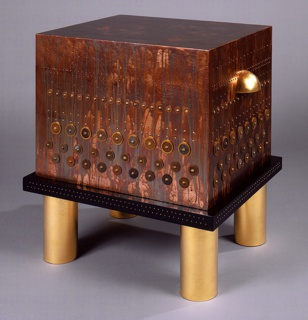 Box-shaped, finished with patinated copper leaf and studded with rows of brass nails, washers, and African coins. Black enameled base resting on four cylindrical gilded feet. Semi-spherical gilded handle on two sides. Top section lifts off.