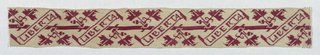 "Cream-colored band embroidered in red with the motto ""Liberta"" contained in a diagonal-shaped scroll. Stylized leaves and acorns appear in between scrolls.."