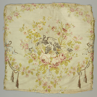 Square fragment of a brocaded silk with a U-shaped floral garland of roses and carnations; heavy rose blossoms are at the bottom of the wreath. Inside are two birds resting on a stringed musical instrument and a bow and a quiver filled with arrows rests nearby. Garland is surrounded by a more delicate ring of flowers that is entwined with a tasseled cord in the lower corners. Ground is cream-colored with a fine red stripe. In the style of Philippe de la Salle.