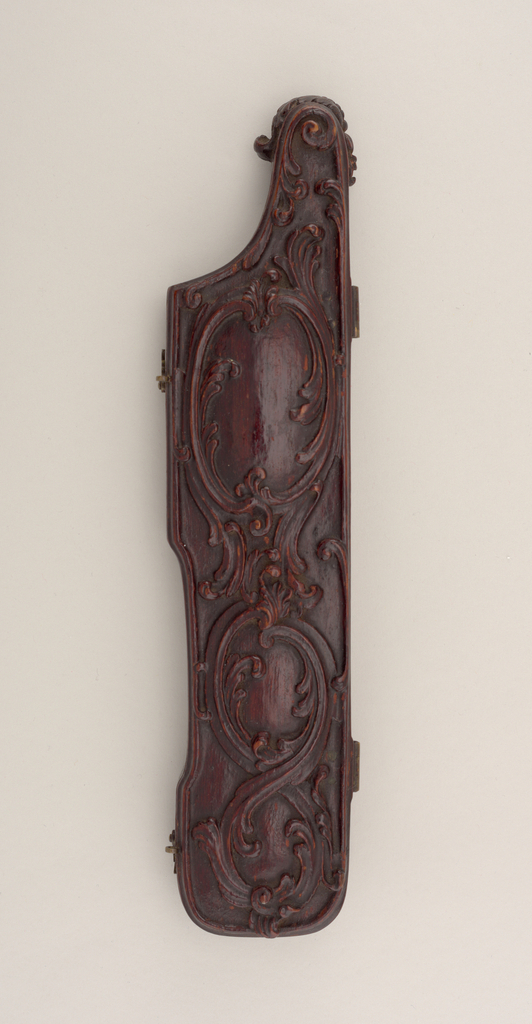 """Mahogany case for three implements, irregular rectangular shape. Lid attached to bottom with two brass hinges and small hooks. Top of lid carved with scrolled acanthus leaves, in the shape of three """"cartouches"""". Inside of case covered with silk, S-shaped scroll on the inside of case to hold the knife in place."""