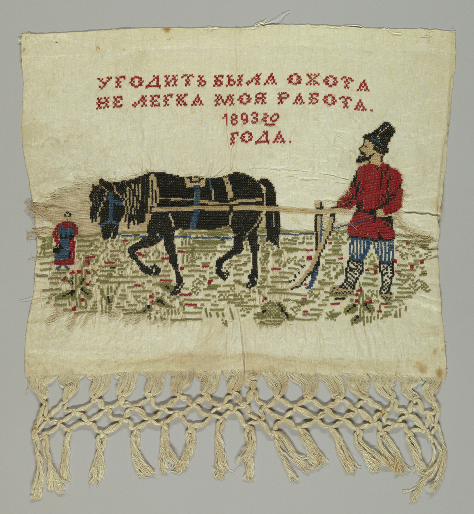 """Man at horse-drawn plough and a woman sowing seeds. Inscription and date in Russian. (Trans: """"One must work hard but it is a pleasure to do one's best."""") Warps at one end are knotted into a fringe."""