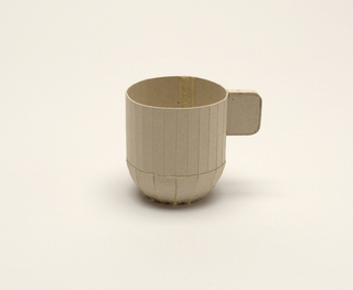 "Cylindrical cup with straight sides, squared D-shaped tab handle and tapered curved base. Cut and scored light gray cardboard; applied paper tape on body and underside; ""1"" penciled on top of tab handle"