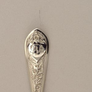 Ovoid bowl with frosted finish to interior. Tapering stem with small gadrooned knop below the pointed, rounded terminal which is stamped with scrolling vines and a dove on a matted ground. Obverse with monogrammed trefoil-topped heart-shaped reserve.