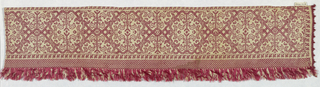 Band with a red embroidered design of angular lines forming hexagons and conventionalized leaves. Border, fringe and edging in red silk.