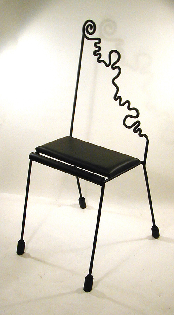 Chair back composed of one straight line of iron on left that leads down to the right in a curly and squiggly diagonal line to the seat of the chair. Seat is flat with thin cushion; straight legs terminate at rubber casters.
