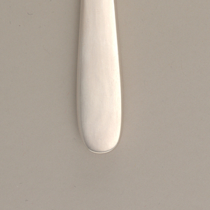 Knife of simple form with curving tapering outline and polished handle; blade serrated on reverse.