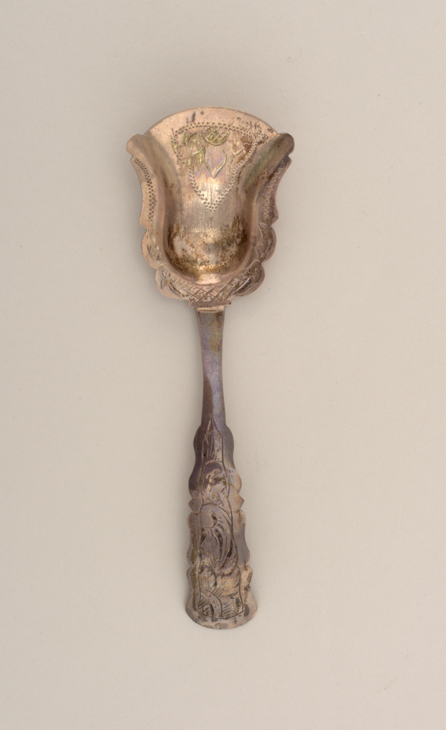 The tea scoop with bell-form, shovel-like bowl with shaped, flat flanged border. The bowl and border engraved with flower and wriggle work. The tapering handle with slightly down-curved, shaped terminal. The terminal obverse engraved with partial flower and scrolls with an oblong reverse.