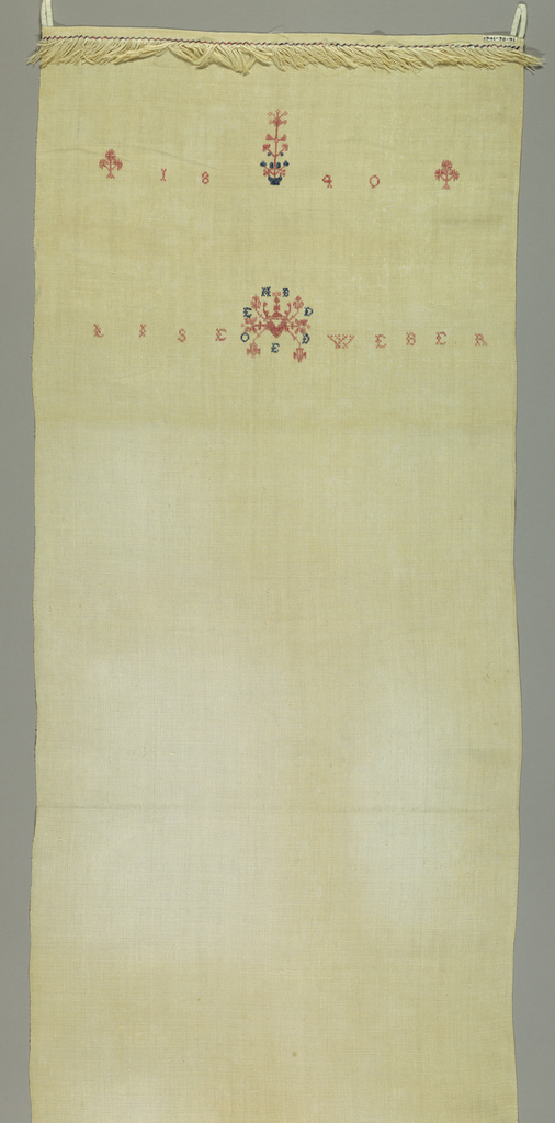 """Towel cover with name, date, ornament with initials around it. Plants and flowers with """"A.F."""" in cross stitch. Fringe on top and bottom."""
