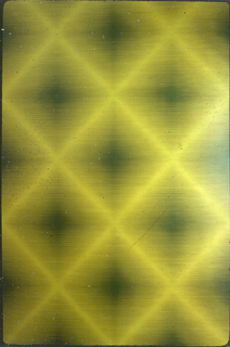 Diamond grid formed by green lines against a yellow, ribbed ground.