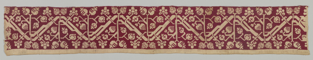 Band with a design of an angular curving vine bearing fruit and leaves. Pattern in reserve on a background in red silk. Fragment from a larger pieces. Upper edge finished with different color silk.