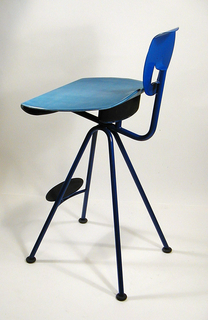 Chair of metal and plastic. Oval blue metal back with opening at center. Round plastic seat with curled back and front. Four metal straight legs that flare from single point under seat terminating at casters; stretcher supporting front two legs above which is a flat oval footrest.