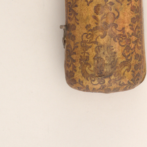 Box for three implements, follows the shape of a spoon. Lid attached to bottom, two hooks and hinges on the front. Top of lid decorated with stamped floral motif. Two cartouches with illegible monograms, a vase with a flower in the centre of the top. Traces of gold. Inside of box covered with suede.