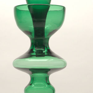 """Nile"" green, exaggerated, almost anthropomorphic baluster form, with bell-shaped base rising with undulating profile to everted top, the tapered conical stopper resting with half in the long neck for support."