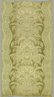 Vertically symmetrical plant forms within a curving border that resembles lace, in bright green, yellow, white and brown.