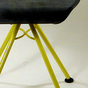Oval yellow metal back with opening at center. Round seat with curled back and front. Four metal straight legs that flare from single point under seat terminating at casters.