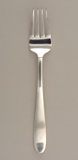 Four-pronged fork of simple form with curving tapering outline and polished surface.