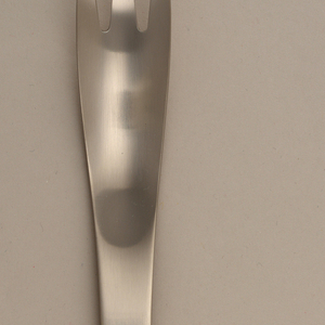 Simple one-piece form of flared three-pronged fork tapering to curved point at end of handle; matte finish.