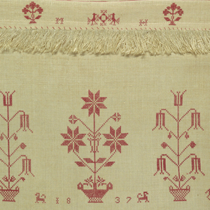 Panel with three horizontal bands of embroidery: the initials M.H., date, birds, plants, animals, and circular ornaments in cross stitch. Three applied fringed bands. Fringe at top and bottom.