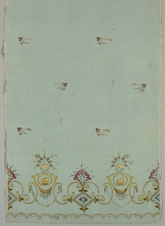 Panel of light blue silk, intended for a skirt, has an embroidered border in colored silks, metallic thread and sequins, and an appliqué of white net. Design of reversed S-curves supporting a heart-shaped frame with a lion masque at the center. Above frame are flower sprays. Narrow border below worked in gold. Above, in the body of the skirt, are detached flower sprigs in rose, blue and brown with metallic thread.