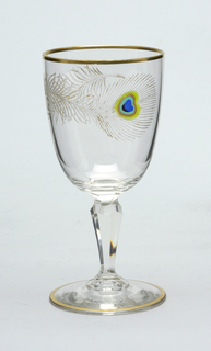 Circular clear glass goblet; etched peacock feather decoration with remnants of gilding; central spot on feather inlaid with roughly circular dot and concentric rings of colors blue, black, aqua, brown green; baluster shaped stem; gilded rim and foot ring.