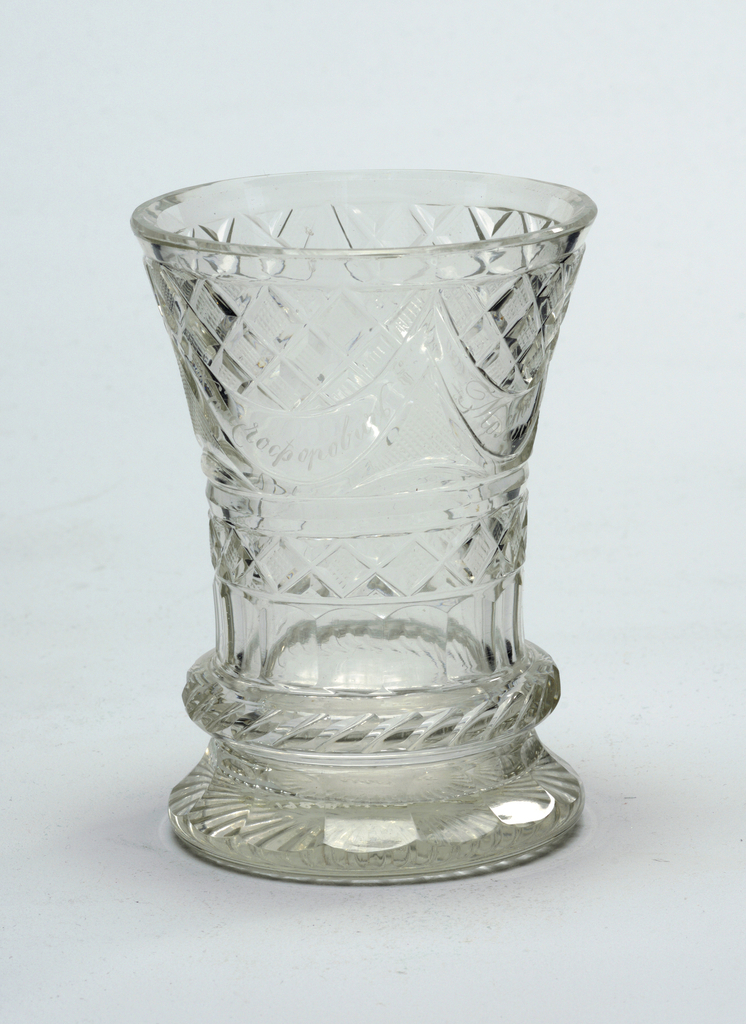 Beaker-shaped body, flared towards top, flared base; cut with wide flutes bottom, a projecting hatched ring above, bands of flutes and strawberry diamonds above that, at top a wide band of swags engraved with an inscrip- tion, strawberry diamonds and fine diamonds above; rayed flutes on bottom.