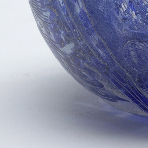 Globular body, on inside an irregularly flecked layer of  blue glass.  Outside deeply etched with large-finned fish, flower shapes and a scalloped collar around the neck.