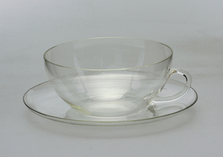 Shallow hemispherical cup with loop handle.  Concave circular saucer.