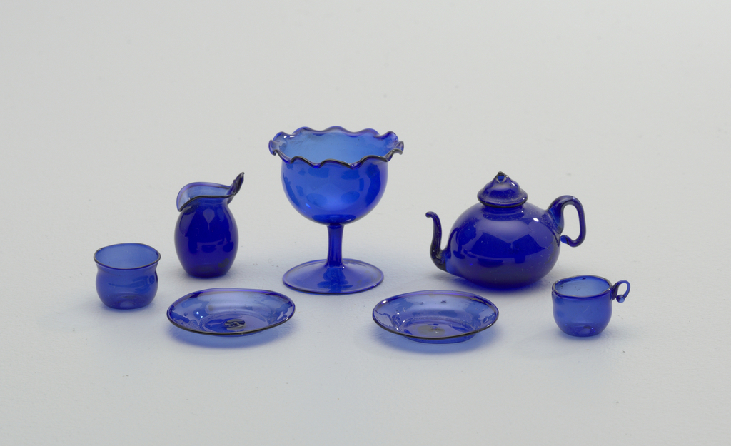 A) Compote: fotted bowl with wavy edge. B) Teapot with bulbous body, dome dover with finial. C) Rounded cup with handle. D) Slop bowl, roundedwith slightly flaring neck. E)F) Two plates. G) Cream pitcher or milk jug with turned-down spout, short handle, possibly broken off.