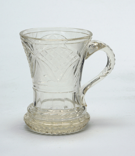 Beaker form, sides flared towards top; cut with 3 arched panels filled with strawberry diamonds and blazes, band of flat fluting and raised ring with blazes below; thick foot cut with vertical fluting sides and straw- berry diamonds; notched loop handle.
