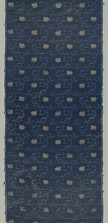 Very fine blue vertically curving branch and ribbon enclosing small multi-color sprigs of flowers on a blue textured background.  Four repeats across width of fabric.  Length of fabric placed side-by-side continue repeat.