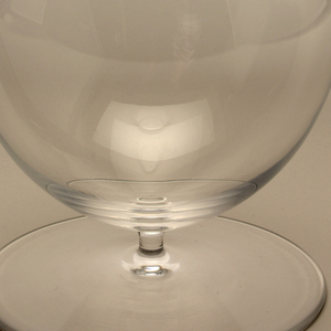 Thin mouth-blown glass with cylindrical neck above an oval bodied bowl on short stem and large circular foot