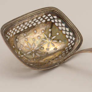 The deep, rounded rectangular bowl pierced with three rosettes surrounded by stars below pierced imbricated border, with stamped finely gadrooned rim. Slightly curving corded handle with flaring squared terminal.