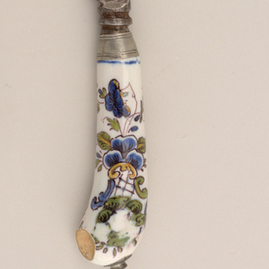 Knife (a): Straight-backed steel blade with rounded, upcurved tip. Pistol grip porcelain handle painted with blue, green and yellow flowers and scrolls out-lined with manganese; fork (b): three prong steel tines and pistol-grip handle painted in blue, green and yellow flowers and foliage within manganesse outlines.