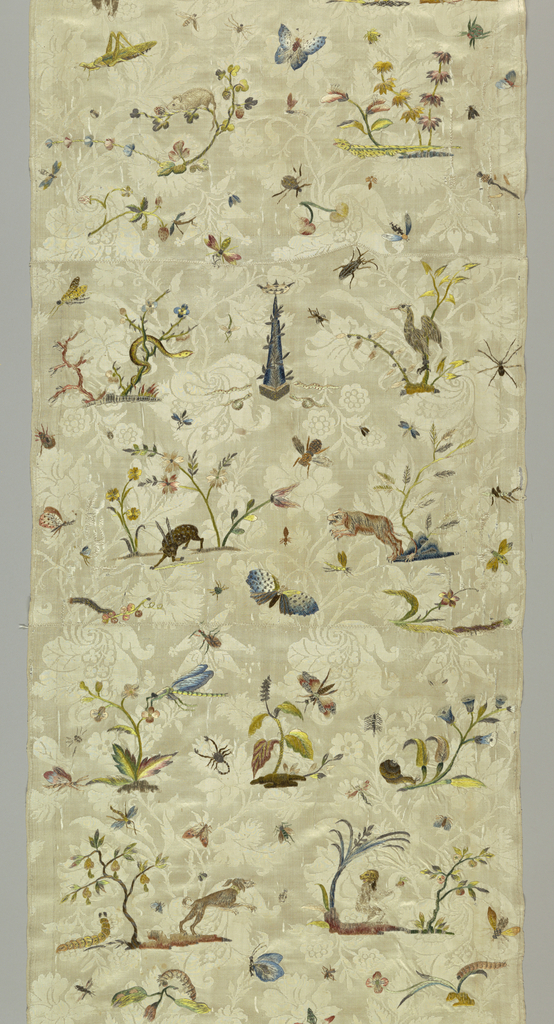 White silk floral damask embroidered with scattered animals, birds and insects in colored silks and metal threads. With an embroidered obelisk surmounted by a coronet with serpents on either side. Composed of four smaller pieces, stitched together.